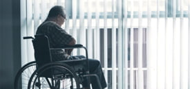 Picture of sad elderly man sitting in the wheelchair in a retirement home